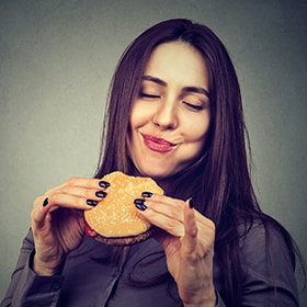 Woman chewing a hamburger evenly to help relieve her TMJ pain