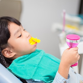 A child receiving fluoride treatment for healthy teeth