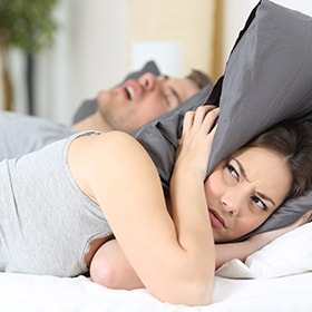 A wife who is tired of her husband's snoring because of him suffering from sleep apnea