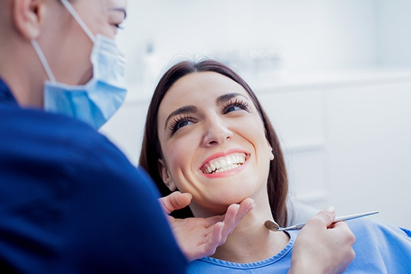A female patient getting a dental cleaning and exam as part of her biannual checkups at the dentist in Peoria, IL