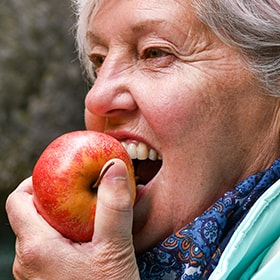 Eating an apple, which is a hard food and may further TMJ pain