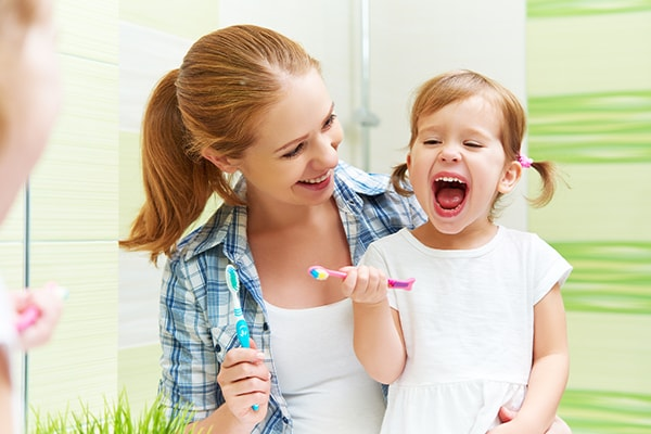 A mother teaching her daughter how to brush her teeth - a part of our general dentistry protocol at our Peoria dental office