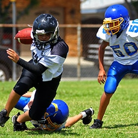 Kids playing football and protecting their teeth with customized mouthguards