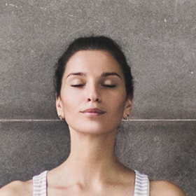 Woman relaxing her face through meditation to help relieve her TMJ pain