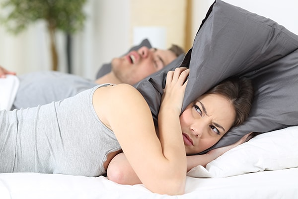 Wife who is tired of her husband's snoring, which is a sign of sleep apnea