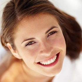 A smiling woman with gorgeous teeth because of porcelain veneers